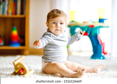 Adorable baby girl playing with educational toys . Happy healthy child having fun with colorful different wooden toy at home. Early development for children with nature toy.