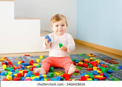 Niña adorable jugando con juguetes educativos. Feliz niño saludable divirtiéndose con coloridos bloques de madera diferentes en casa en la habitación doméstica. Colores y formas de aprendizaje para bebés
