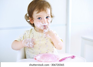 Adorable baby girl playing with food. Child eating yogurt. Dirty face of happy kid. Portrait of a baby eating with a stained face.