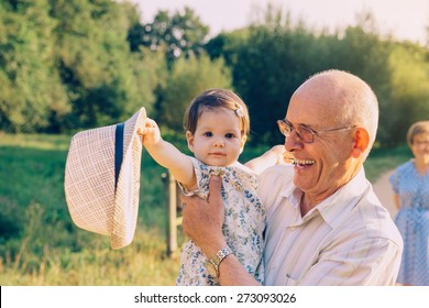 Adorable baby girl playing with the hat of senior man over a nature background. Two different generations concept.