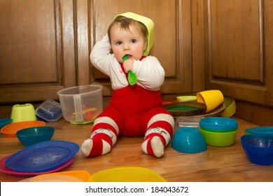 Adorable baby girl pulling pots and pans and other dishes out of a kitchen cupboard.