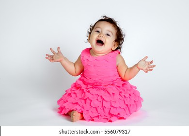 An adorable, baby girl sits in a pink, frilly, layered dress with an excited, surprise expression.  She has her hands out to the side and head tilted back.