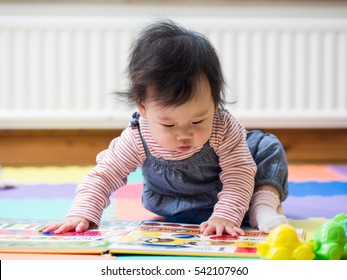 Adorable baby girl sitting on play mat  and reading book at home
