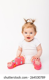 Adorable baby girl sitting wearing pink leg warmers.