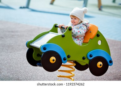Adorable baby girl sitting in a wooden car on outdoor playground on sunny autumn day