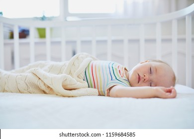 Adorable baby girl sleeping in co-sleeper crib attached to parents' bed. Little child having a day nap in cot. Infant kid in sunny nursery