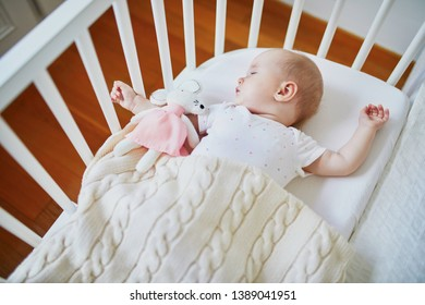 Adorable baby girl sleeping in co-sleeper crib attached to parents' bed with stuffed toy. Little child having a day nap in cot. Sleep training concept. Infant kid in sunny nursery