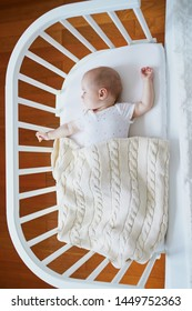 Adorable baby girl sleeping in co-sleeper crib attached to parents' bed. Little child having a day nap in cot. Sleep training concept. Infant kid in sunny nursery