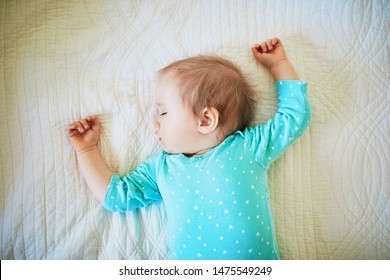 Adorable baby girl sleeping in crib. Small kid having day nap in parents bed
