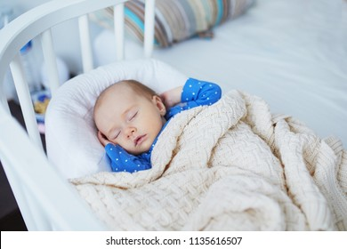 Adorable baby girl sleeping under knitted blanket in co-sleeper bed