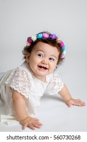 An adorable baby girl smiles with a contagious grin.  She is wearing a floral headband and wearing white on a white photo background in a portrait studio.