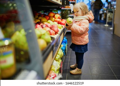 Adorable baby girl in supermarket selecting apples. Little child going shopping. Kid in large food or grocery store