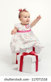 Adorable baby girl with two gift boxes posing over white background