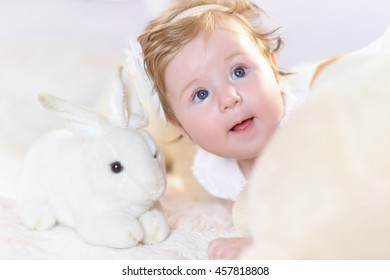 Adorable baby girl in white and pink sunny bedroom. Newborn child relaxing in bed. Family morning at home. New born kid with toys. Portrait little cheerful child laugh. Happy sweet cute face.