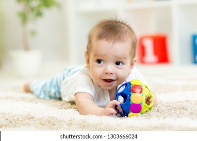 Adorable baby having fun with toy on cozy rug. Happy cheerful kid boy playing on the floor