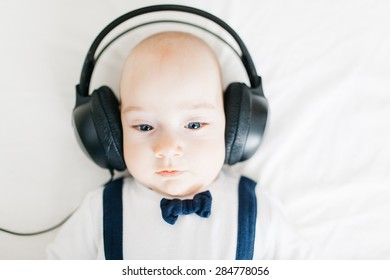 Adorable  baby listens to music through headphones. Close-up.