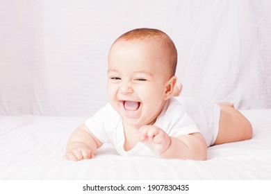 Adorable baby lying on the stomach at the white