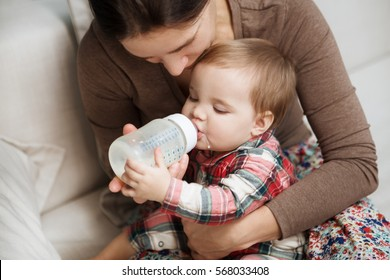 Adorable baby with a milk bottle. Baby milk eating bottle