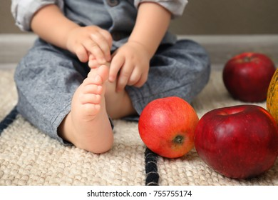 Adorable baby near ripe apples indoors