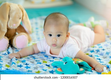 Adorable baby on bedroom on morning. Newborn 5 months child relaxing in bed. New born kid during tummy time with stuffed animal toys.