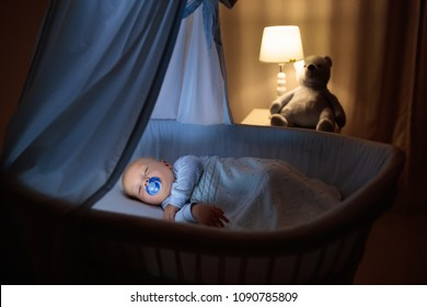 Adorable baby with pacifier sleeping in blue bassinet with canopy at night. Little boy in pajamas taking nap in dark room with crib, lamp and toy bear. Bed time for kids. Bedroom and nursery interior