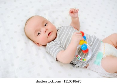 Adorable baby portrait holding rattle in bright contrasting colors, infants cognitive development skills