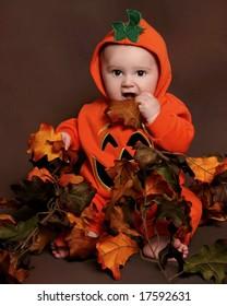adorable baby in a pumpkin halloween costume