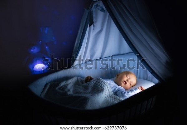 Adorable baby sleeping in blue bassinet with canopy at night. Little boy in pajamas getting ready to sleep in dark room with crib, lamp and toy bear. Bed time for kids