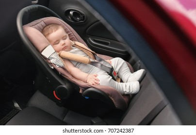 Adorable baby sleeping in child safety seat inside of car