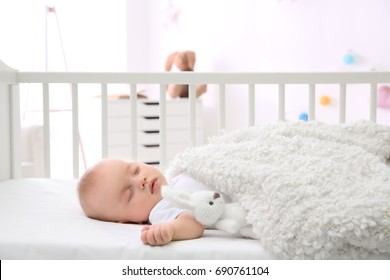 Adorable baby sleeping in cradle at home