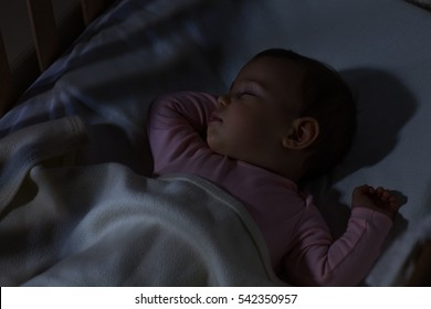 Adorable baby sleeping at night. Little girl in pajama taking a nap in dark room / Baby Sleeping on the bed