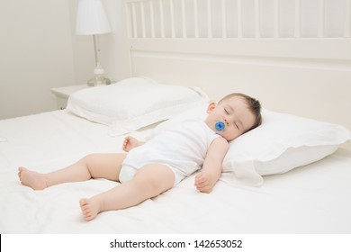 Adorable baby sleeping relaxed and sprawl in parent's bed