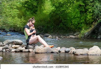 Adorable baby sleeping in a wrap, sling in her mothers arms on riverside during summer vacation, relaxation time and happiness