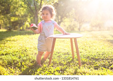 Adorable baby standing in the park and holding the peace of watermelon,in the beautiful summer  day