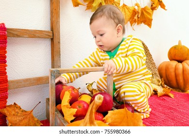 Adorable baby in striped pajamas and basket with apples indoors