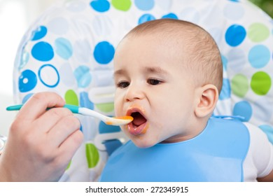 Adorable baby taking bite of food