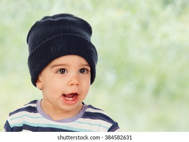 Adorable baby with wool cap and green background
