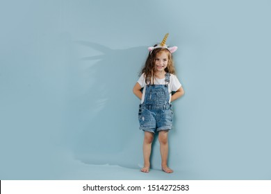 Adorable barefoot little preschooler girl with brown wavy hair is wearing cute unicorn headband, leaning against blue wall. Shadow resembles unicorn outlines.