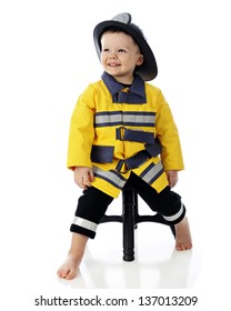An adorable, barefoot toddler happily leaning on a stool in his fireman outfit.  On a white background.