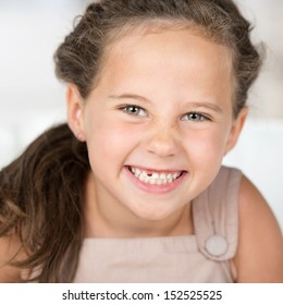 Adorable beautiful little girl grinning at the camera showing off her missing front tooth, close up portrait