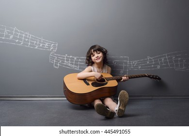 Adorable beauty plays the guitar with the light smile on her face. Big acoustic musical instrument in childish small hands. Painted with chalk stave on the neutral background.