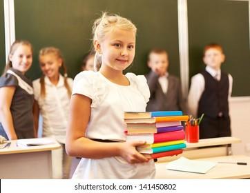Adorable best schoolgirl  holding books  over classmates