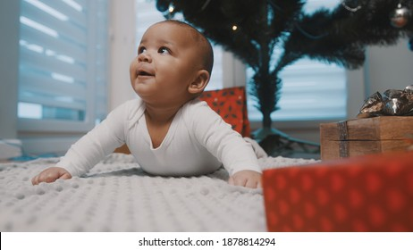 Adorable black baby having a tummy time under the christmas tree surrounded by presents. First baby christmas. High quality photo