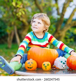 Adorable blond kid boy sitting with traditional jack-o-lantern for halloween in autumn garden, outdoors. Child having fun on sunny warm october day. Creative and active leisure