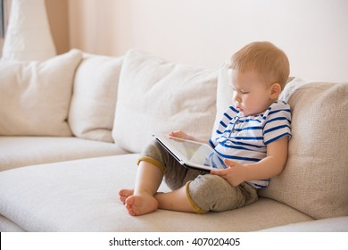Adorable blond toddler boy laying on the sofa and playing with pc at home, indoors. Child with tablet computer.