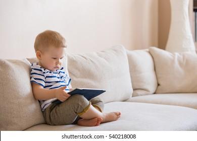 Adorable petit garçon blond allongé sur le canapé et jouant avec une tablette à la maison, à l'intérieur. Enfant avec tablette.