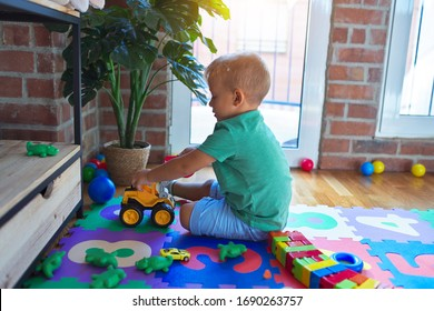 Adorable blond toddler playing around lots of toys at kindergarten