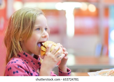 Adorable blonde cheerful girl in pink clothes eat double burger with beef and cheese in fast food restaurant