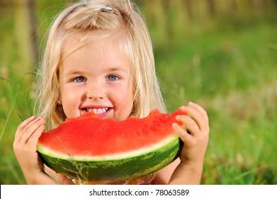 Adorable blonde girl eats a watermelon outdoors
