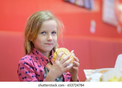 Adorable blonde girl in pink clothes eat double burger with beef and cheese in fast food restaurant